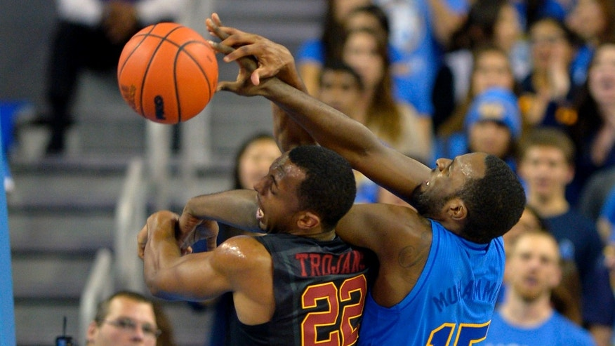 Southern California guard Byron Wesley, left, and UCLA guard/forward Shabazz Muhammad battle for a rebound during the first half of their NCAA college basketball game, Wednesday, Jan. 30, 2013, in Los Angeles.  (AP Photo/Mark J. Terrill)