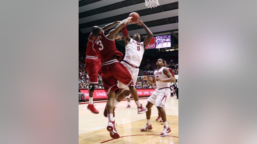 Alabama guard Trevor Lacey (5) takes a shot while Arkansas guard Rickey Scott (3) blocks during an NCAA college basketball game in Tuscaloosa, Ala., Thursday, Jan. 31, 2013. (AP Photo/Tuscaloosa News, Michelle Lepianka Carter)