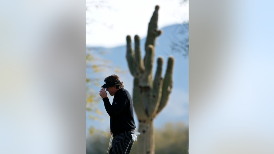 With a saguaro cactus dwarfing him in the background, Phil Mickelson tips his visor to the crowd after making a birdie on the 12th hole during the first round of the Waste Management Phoenix Open golf tournament Thursday, Jan. 31, 2013, in Scottsdale, Ariz. (AP Photo/Ross D. Franklin)