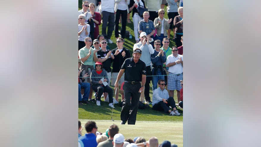 Phil Mickelson reacts to the crowd after missing a birdie putt on the ninth green during the first round of the Waste Management Phoenix Open golf tournament, Thursday, Jan. 31, 2013, in Scottsdale, Ariz. (AP Photo/Matt York)