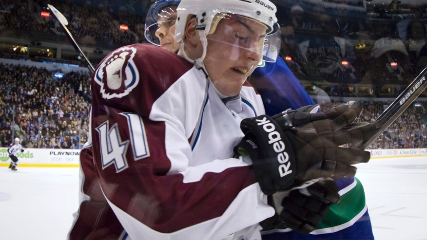 Colorado Avalanche's Tyson Barrie is checked into the boards by Vancouver Canucks' Mason Raymond, back, during an NHL hockey game in Vancouver, British Columbia, on Wednesday, Jan. 30, 2013. (AP Photo/The Canadian Press, Darryl Dyck)