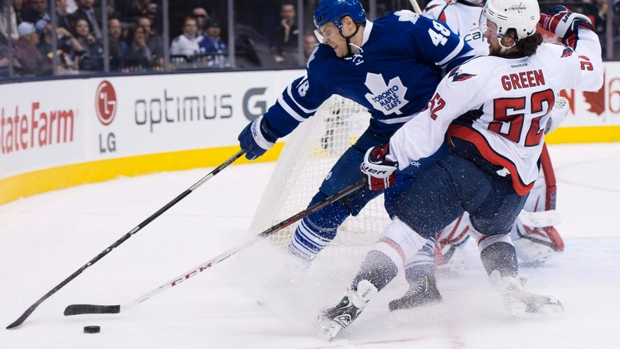 Toronto Maple Leafs forward Ryan Hamilton, left, battles for the puck against Washington Capitals defenseman Mike Green, right, during the second period of an NHL hockey game in Toronto on Thursday, Jan. 31, 2013. (AP Photo/The Canadian Press, Nathan Denette)