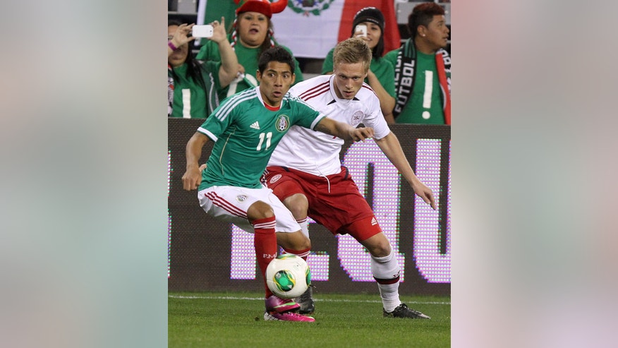 Mexico mid-feilder Javier Aquino (11) shields Denmark midfielder Nicolai Jorgensen (9) from the ball during the first half of an international friendly soccer match on Wednesday, Jan. 30, 2013, in Glendale, Ariz. (AP Photo/Rick Scuteri)