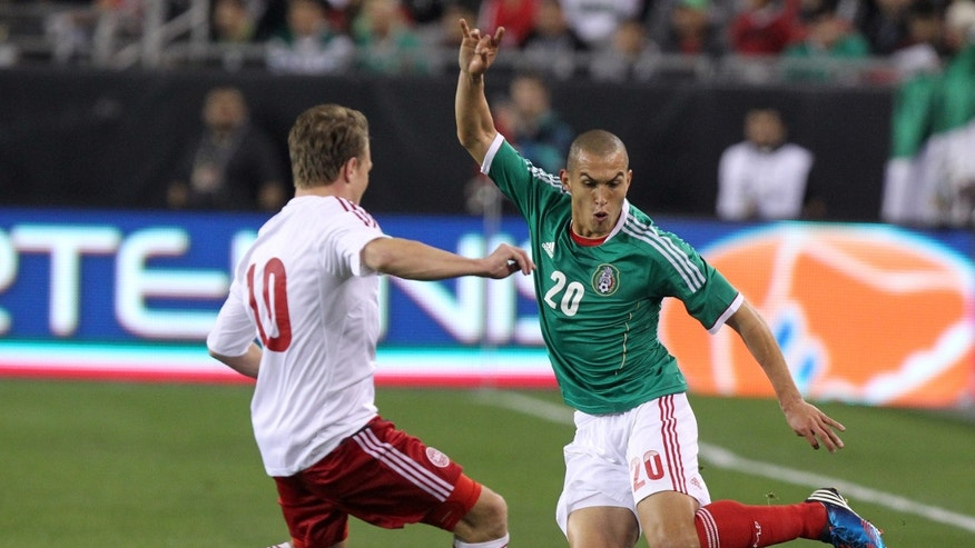 Mexico defenseman Jorge Torres Nilo (20), right, challenges Denmark mid-fielder Emil Larsen (10) during the first half of an international friendly soccer match on Wednesday, Jan. 30, 2013, in Glendale, Ariz. (AP Photo/Rick Scuteri)