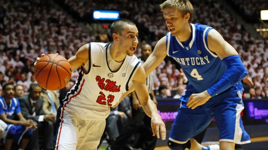 Mississippi guard Marshall Henderson (22) drives up court past Kentucky guard Jon Hood (4) in the first half of their NCAA college basketball game, Tuesday, Jan. 29, 2013 in Oxford, Miss.  Kentucky won 87-74. (AP Photo/Rogelio V. Solis)