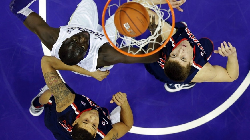 Washington's Aziz N'Diaye, top left, watches his shot got in as Arizona's Kaleb Tarczewski, right, and Brandon Ashley, lower left, look on in the first half of an NCAA college basketball game, Thursday, Jan. 31, 2013, in Seattle. (AP Photo/Ted S. Warren)