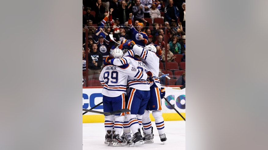 Edmonton Oilers' Lennart Petrell, middle, of Finland, celebrates his goal against the Phoenix Coyotes with teammates, including Sam Gagner (89), during the first period in an NHL hockey game Wednesday, Jan. 30, 2013, in Glendale, Ariz. (AP Photo/Ross D. Franklin)