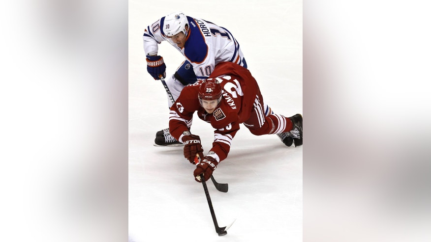 Phoenix Coyotes' Oliver Ekman-Larsson (23), of Sweden, is tripped by Edmonton Oilers' Shawn Horcoff (10) as he tries to keep control of the puck during the second period in an NHL hockey game Wednesday, Jan. 30, 2013, in Glendale, Ariz. (AP Photo/Ross D. Franklin)
