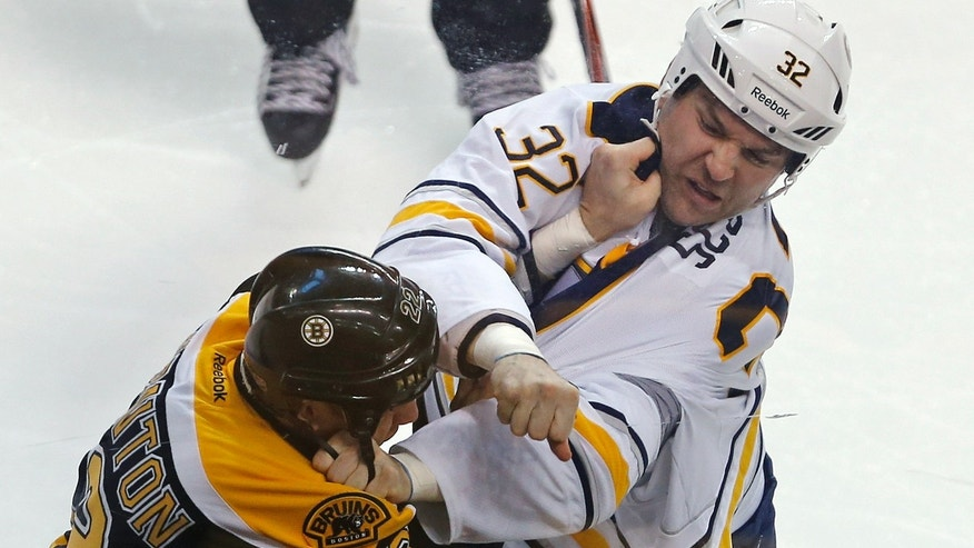 Buffalo Sabres left wing John Scott (32) follows through after landing a punch during a fight with Boston Bruins right wing Shawn Thornton, left, during the first period of an NHL hockey game in Boston, Thursday, Jan. 31, 2013. (AP Photo/Charles Krupa)