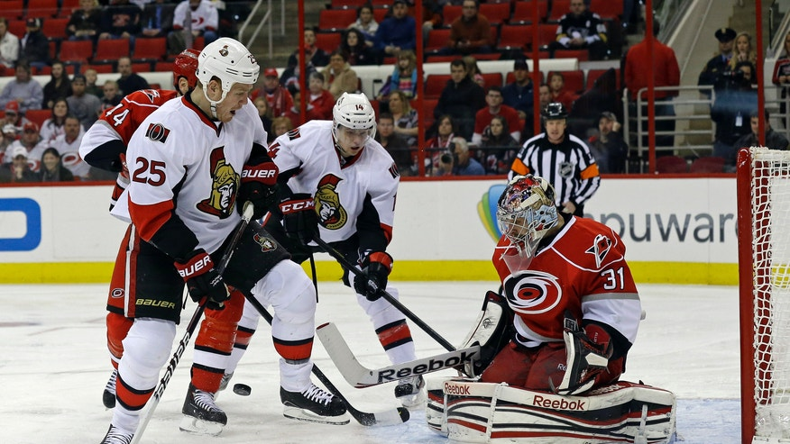 Carolina Hurricanes goalie Dan Ellis (31) deflects the puck as Ottawa Senators' Chris Neil (25) and Colin Greening (14) during the first period of an NHL hockey game, Friday, Feb. 1, 2013, in Raleigh, N.C. (AP Photo/Gerry Broome)