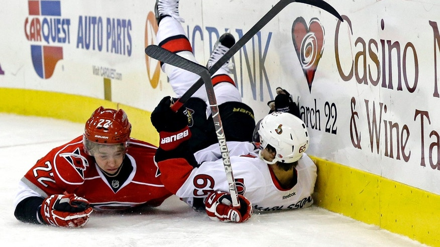 Carolina Hurricanes' Zac Dalpe (22) and Ottawa Senators' Erik Karlsson (65), of Sweden, fall to the ice while chasing the puck during the second period of an NHL hockey game in Raleigh, N.C., Friday, Feb. 1, 2013. (AP Photo/Gerry Broome)