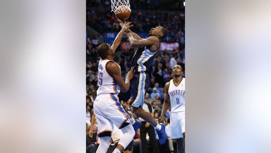 Memphis Grizzlies guard Tony Allen, center, shoots between Oklahoma City Thunder forward Kevin Durant (35) and forward Serge Ibaka (9) during the first quarter of an NBA basketball game in Oklahoma City, Thursday, Jan. 31, 2013. (AP Photo/Sue Ogrocki)