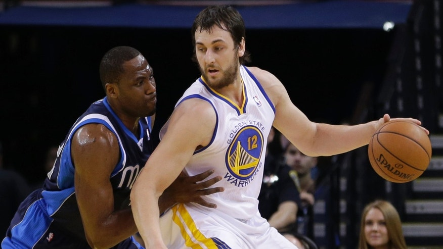 Golden State Warriors' Andrew Bogut, right, drives the ball against Dallas Mavericks' Elton Brand in the first half of an NBA basketball game Thursday, Jan. 31, 2013, in Oakland, Calif. (AP Photo/Ben Margot)