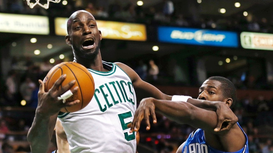 Boston Celtics forward Kevin Garnett (5) grabs a rebound against Orlando Magic forward Andrew Nicholson (44) during the first quarter of an NBA basketball game in Boston, Friday, Feb. 1, 2013. (AP Photo/Charles Krupa)
