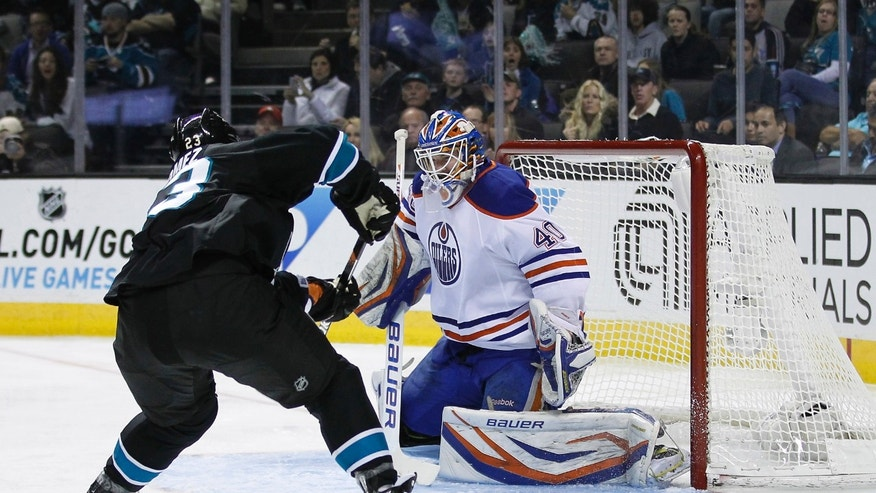 Edmonton Oilers goalie Devan Dubnyk (40) deflects a shot on goal by San Jose Sharks center Scott Gomez (23) during the first period of an NHL hockey game in San Jose, Calif., Thursday, Jan. 31, 2013. (AP Photo/Tony Avelar)