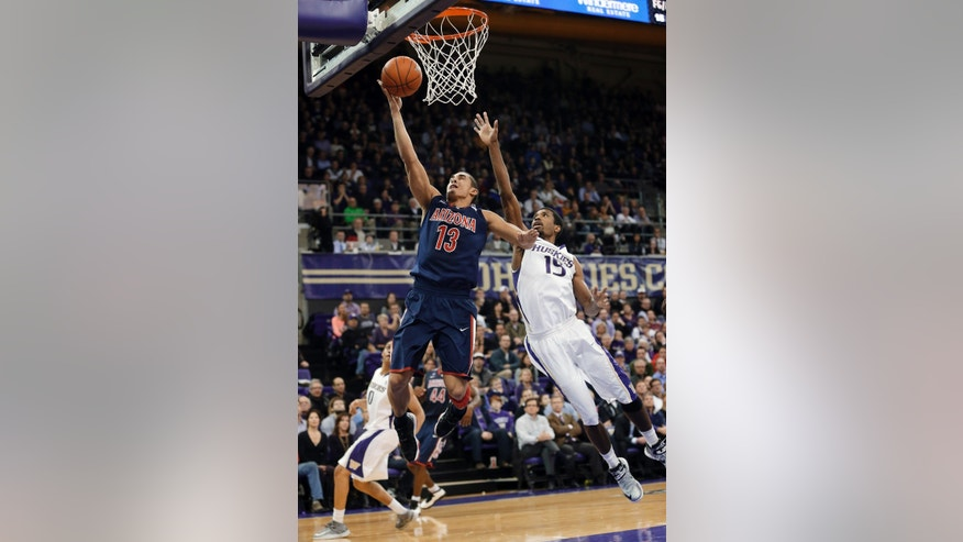 Arizona's Nick Johnson (13) puts up a shot as Washington's Scott Suggs (15) defends in the second half of an NCAA college basketball game, Thursday, Jan. 31, 2013, in Seattle. Arizona won 57-53. (AP Photo/Ted S. Warren)