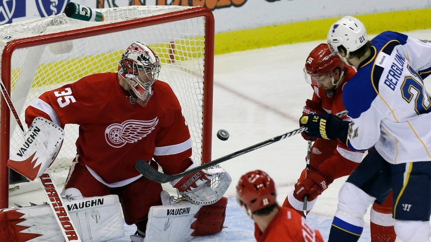 St. Louis Blues center Patrik Berglund (21), of Sweden, gets the puck past Detroit Red Wings defenseman Niklas Kronwall (55), of Sweden, and goalie Jimmy Howard (35) for a goal during the second period of an NHL hockey game in Detroit, Friday, Feb. 1, 2013. (AP Photo/Carlos Osorio)