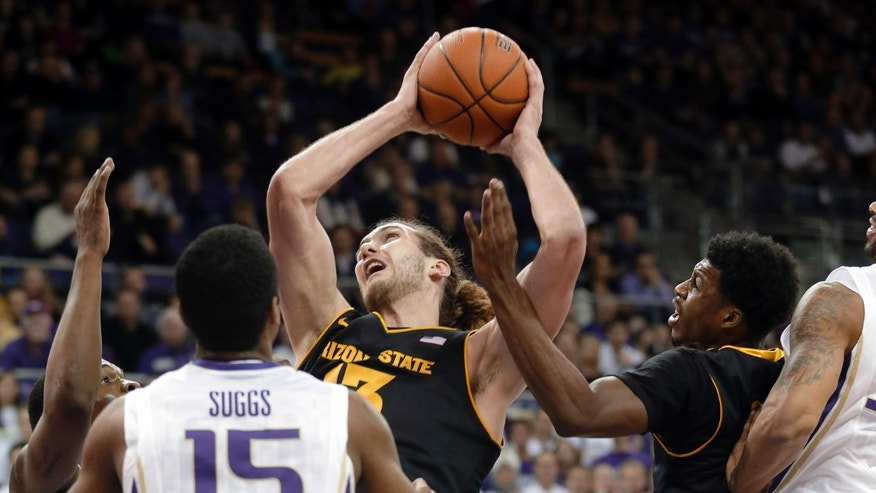 Arizona State's Jordan Bachynski, center, looks to pass under pressure from Washington's Scott Suggs (15) as Arizona State's Carrick Felix looks on at right, in the first half of an NCAA college basketball game, Saturday, Feb. 2, 2013, in Seattle. (AP Photo/Ted S. Warren)