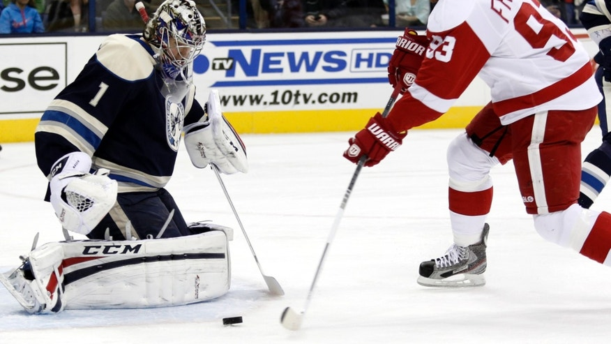 Detroit Red Wings' Johan Franzen, right, of Sweden, shoots the puck against Columbus Blue Jackets goalie Steve Mason in the first period of an NHL hockey game in Columbus, Ohio, Saturday, Feb. 2, 2013. Franzen scored on the play. (AP Photo/Paul Vernon)