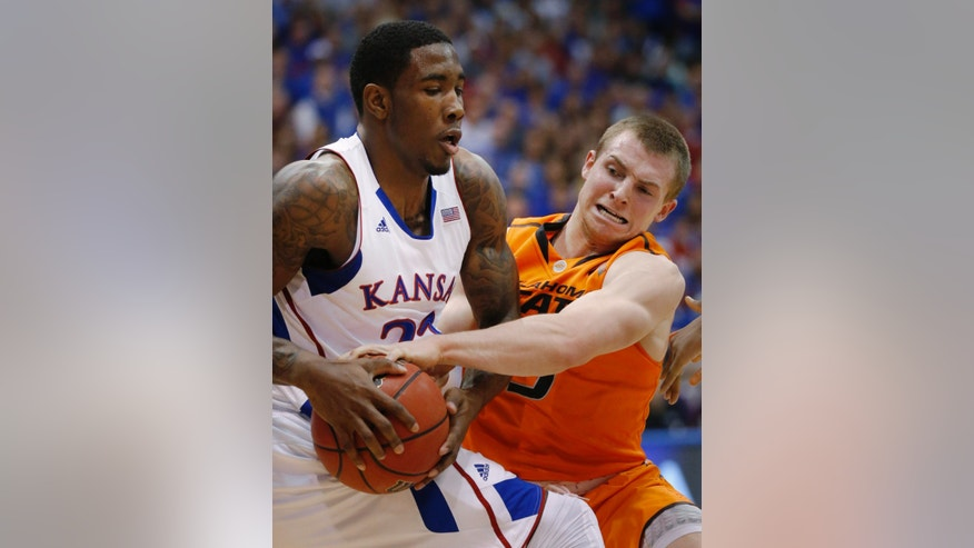 Kansas forward Jamari Traylor (31) keeps the ball away from Oklahoma State guard Phil Forte (13) during the first half of an NCAA college basketball game in Lawrence, Kan., Saturday, Feb. 2, 2013. (AP Photo/Orlin Wagner)