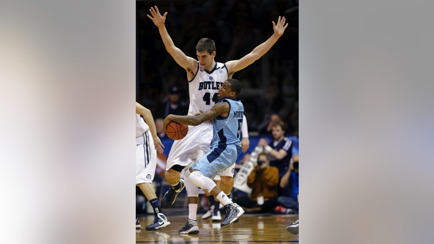 Rhode Island guard Xavier Munford (5) crashes into Butler center Andrew Smith in the first half of an NCAA college basketball game in Indianapolis, Saturday, Feb. 2, 2013. (AP Photo/Michael Conroy)