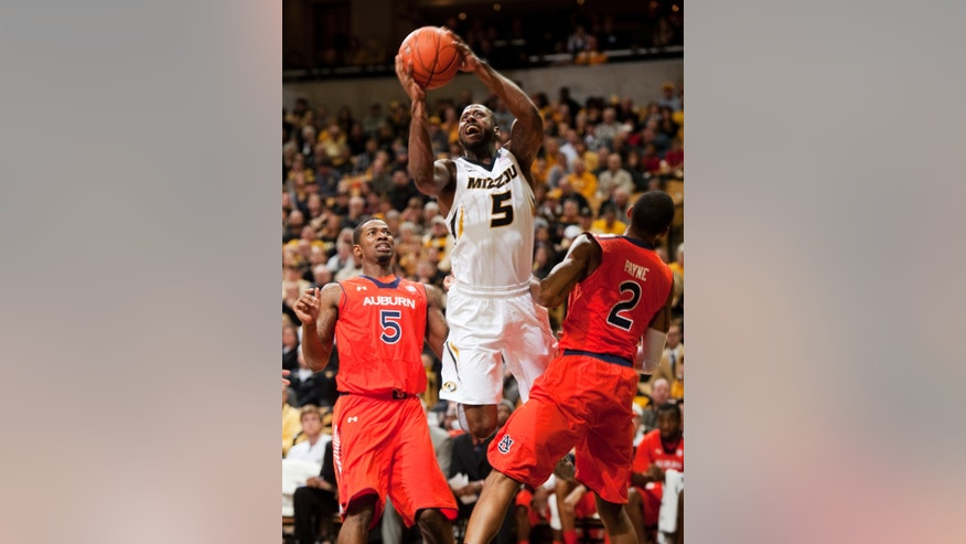 Missouri's Keion Bell, center, is fouled as he shoots between Auburn's Allen Payne, right, and Shaquille Johnson, left, during the first half of an NCAA college basketball game Saturday, Feb. 2, 2013, in Columbia, Mo. (AP Photo/L.G. Patterson)