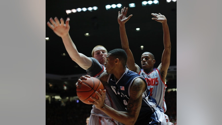 Nevada's Devonte Elliott, middle, is pressured by New Mexico's Alex Kirk, left, and Chad Adams in the first half of an NCAA college basketball game on Saturday, Feb. 2, 2013, in Albuquerque, N.M. (AP Photo/Jake Schoellkopf)