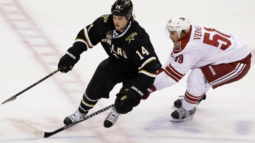 Dallas Stars' jamie Benn (14) and Phoenix Coyotes center Antoine Vermette (50) compete for a loose puck in the third period of an NHL hockey game on Friday, Feb. 1, 2013, in Dallas. The Stars won in a shootout 4-3. (AP Photo/Tony Gutierrez)