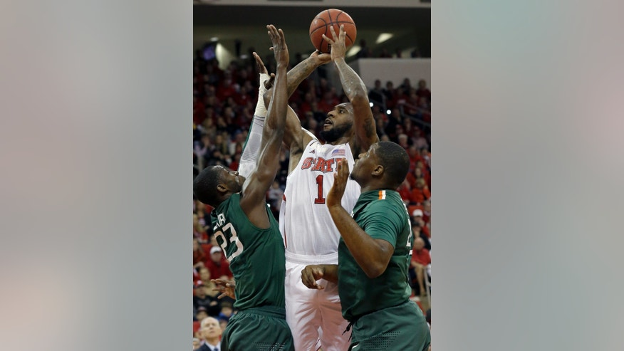 North Carolina State's Richard Howell (1) shoots as Miami's Tonye Jekiri (23) and Reggie Johnson defend during the first half of an NCAA college basketball game in Raleigh, N.C., Saturday, Feb. 2, 2013. (AP Photo/Gerry Broome)
