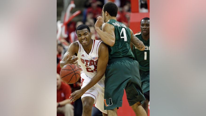 North Carolina State's T.J. Warren (24) passes around Miami's Trey McKinney Jones (4) during the first half of an NCAA college basketball game in Raleigh, N.C., Saturday, Feb. 2, 2013. (AP Photo/Gerry Broome)