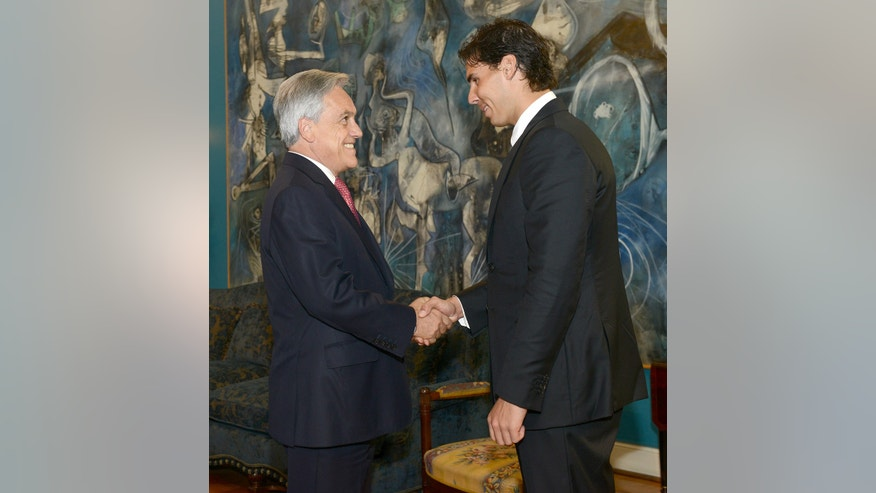 In this photo released by Chile's Presidential Press Office, Spain's tennis player Rafael Nadal, right, shakes hands with Chile's President Sebastian Pinera at the La Moneda presidential palace in Santiago, Chile, Friday, Feb. 1, 2013. Nadal arrived in Chile on Friday and will test his injured left knee in competition for the first time next week after sitting out for seven months, the longest break of his career. (AP Photo/Chile's Presidential Press Office)