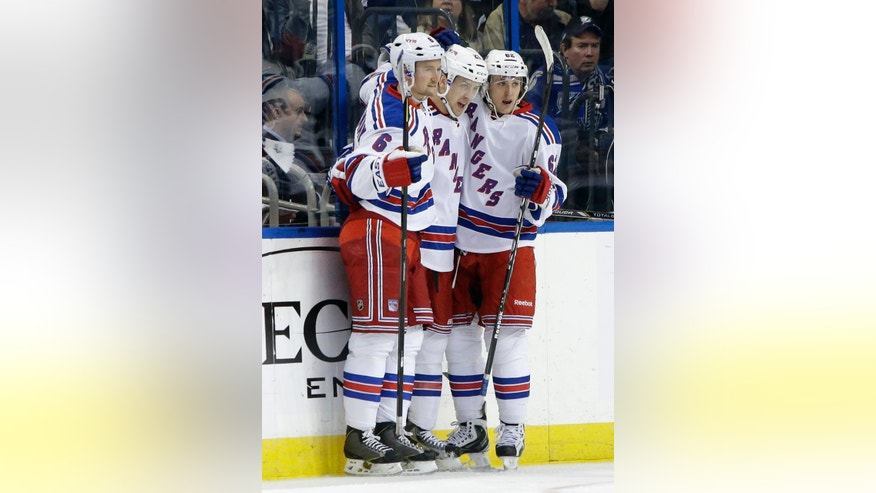 New York Rangers center Derek Stepan, center, celebrates with teammates Anton Stralman, left, and Carl Hagelin, right, after scoring against the Tampa Bay Lightning during the second period of an NHL hockey game on Saturday, Feb. 2, 2013, in Tampa, Fla. (AP Photo/Chris O'Meara)