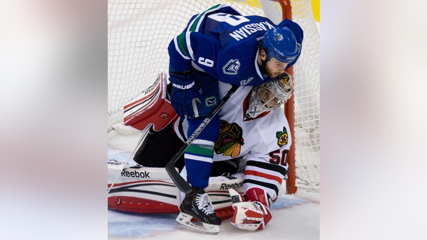 Vancouver Canucks' Zack Kassian, top, falls on Chicago Blackhawks goalie Corey Crawford during the second period of an NHL hockey game in Vancouver, British Columbia, on Friday, Feb. 1, 2013. (AP Photo/The Canadian Press, Darryl Dyck)