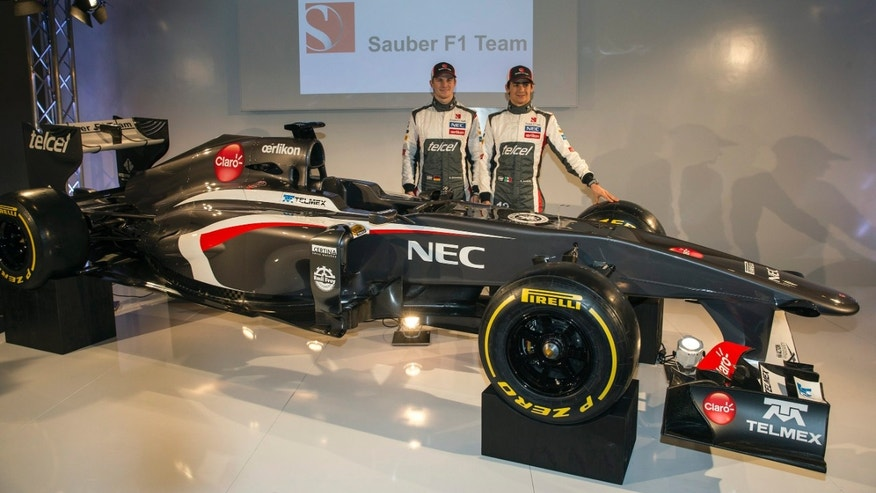 Sauber F1 Team Formula One drivers Nico Huelkenberg of Germany, left, and fellow team member Esteban Gutierrez of Mexico, right, pose with  the Sauber C32-Ferrari, the newly unveiled Sauber F1 Team Formula One car for the 2013 season, during the launch in Hinwil, Switzerland, on Saturday, Feb. 2, 2013. (AP Photo/Keystone/Patrick B. Kraemer)