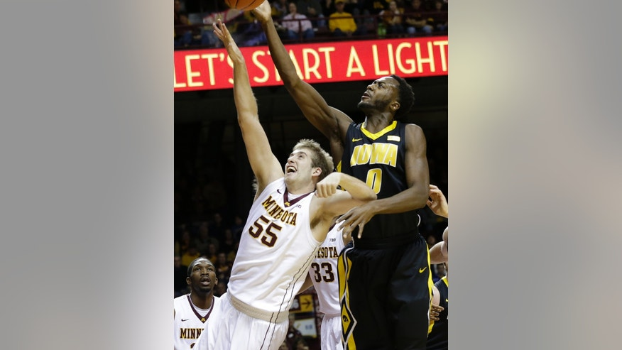Iowa's Gabriel Olaseni, right, lays up over the outstretched arm of Minnesota's Elliott Eliason in the first half of an NCAA college basketball game on Sunday, Feb. 3, 2013, in Minneapolis. (AP Photo/Jim Mone)