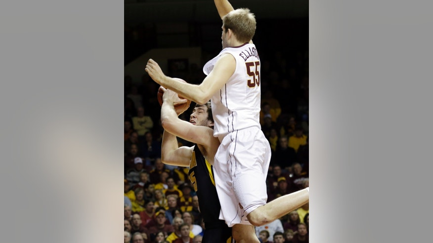 Iowa's Zach McCabe, left, protects the ball as Minnesota's Elliott Eliason looms over him in the first half of an NCAA college basketball game on Sunday, Feb. 3, 2013, in Minneapolis. (AP Photo/Jim Mone)