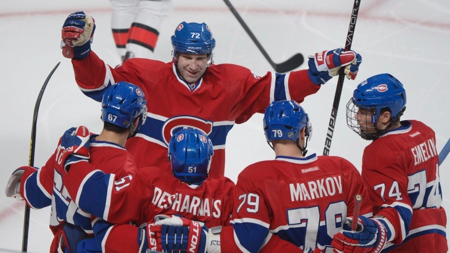 Montreal Canadiens' David Desharnais (51) celebrates with teammates Max Pacioretty (67), Andrei Markov (79) Alexei Emelin (74) and Erik Cole (72) after scoring against the Ottawa Senators' during first period NHL hockey action in Montreal, Sunday, Feb. 3, 2013. THE CANADIAN PRESS IMAGES/Graham Hughes.