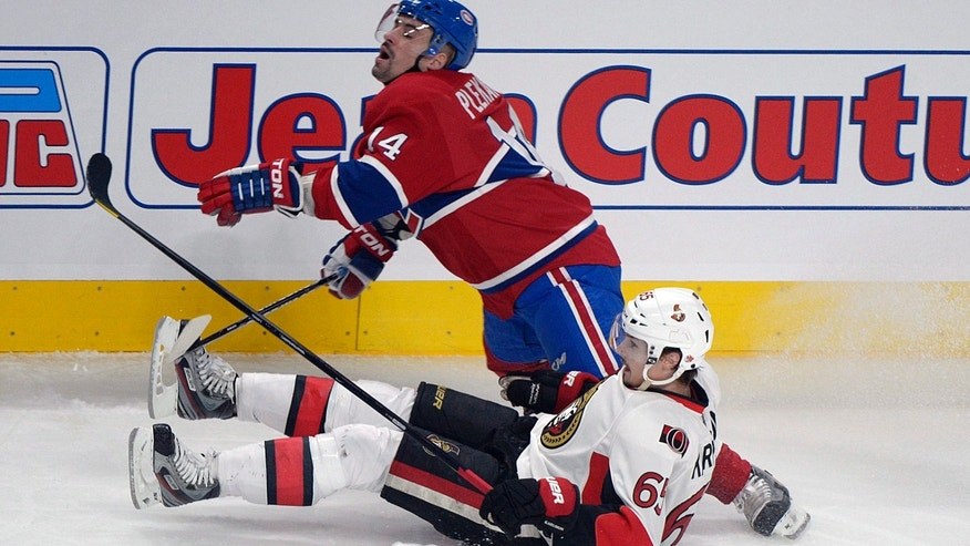 Montreal Canadiens' Tomas Plekanec (14) collides with Ottawa Senators' Erik Karlsson during second period NHL hockey action in Montreal Sunday Feb. 3, 2013. (AP Photo/THE CANADIAN PRESS IMAGES,Graham Hughes)