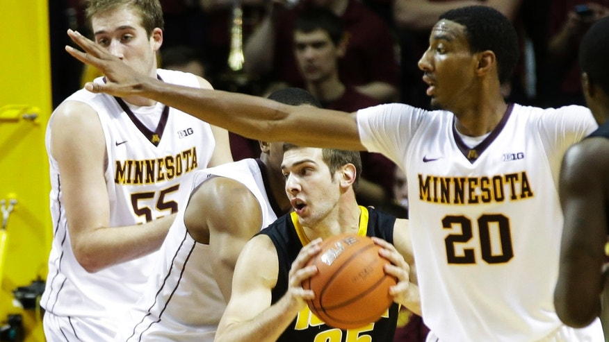 Iowa's Eric May (25) looks for help as he is pressured by Minnesota players, including Minnesota's Elliott Eliason (55) and  Austin Hollins (20), in the second half of an NCAA college basketball game on Sunday, Feb. 3, 2013, in Minneapolis. Minnesota won 62-59. May scored 10 points for Iowa while Hollins led Minnesota with 17. (AP Photo/Jim Mone)