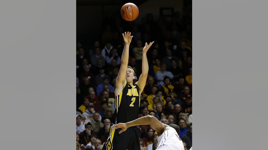 Iowa's Josh Oglesby shoots over a fallen Minnesota defender in the first half of an NCAA college basketball game on Sunday, Feb. 3, 2013, in Minneapolis. Minnesota won 62-59.  (AP Photo/Jim Mone)