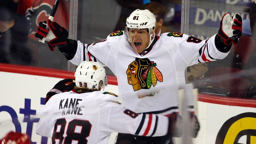 Chicago Blackhawks' Marian Hossa, right, from Slovakia, celebrates his goal with teammate Patrick Kane during overtime of an NHL hockey game in Calgary, Alberta, Saturday, Feb. 2, 2013. The Blackhawks defeated the Flames 3-2 in a shootout. (AP Photo/The Canadian Press, Jeff McIntosh)