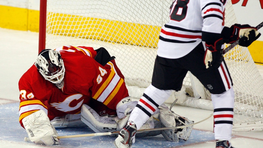 Chicago Blackhawks' Patrick Kane, right, scores the winning goal on Calgary Flames goalie Miikka Kiprusoff, from Finland, during overtime of an NHL hockey game in Calgary, Alberta, Saturday, Feb. 2, 2013. The Blackhawks defeated the Flames 3-2 in a shootout. (AP Photo/The Canadian Press, Jeff McIntosh)