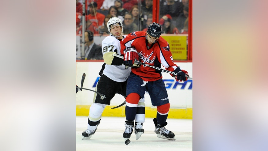 Washington Capitals center Mike Ribeiro (9) fights for the puck against Pittsburgh Penguins center Sidney Crosby (87) during the second period of an NHL hockey game on Sunday, Feb. 3, 2013, in Washington. (AP Photo/Nick Wass)