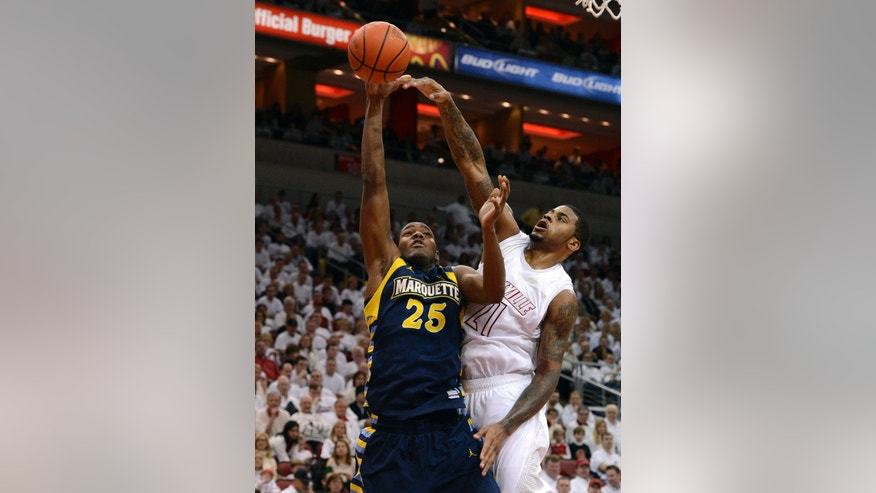 Louisville's Chane Behanan, right, blocks the shot of Marquette's Steve Taylor Jr. during the first half of their NCAA college basketball game, Sunday, Feb. 3, 2013, in Louisville, Ky. (AP Photo/Timothy D. Easley)