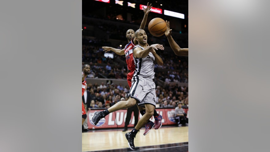 San Antonio Spurs' Tony Parker, right, of France, passes the ball as Washington Wizards' A.J. Price (12) tries to defend him from behind during the first half of an NBA basketball game, Saturday, Feb. 2, 2013, in San Antonio. (AP Photo/Eric Gay)
