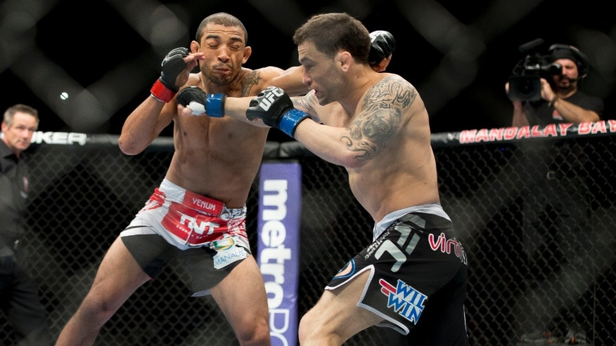 Jose Aldo, of Rio de Janeiro, left, trades punches with Frankie Edgar during their UFC 156 featherweight mixed martial arts title match, Saturday, Feb. 2, 2013 at The Mandalay Bay Resort & Casino in Las Vegas. Aldo won by unanimous decision. (AP Photo/Eric Jamison)