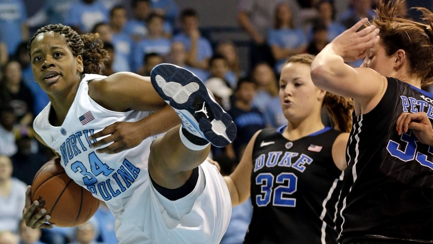 Duke's Tricia Liston (32) and Haley Peters, right, defend as North Carolina's Xylina McDaniel (34) pulls down a rebound during the first half of an NCAA college basketball game in Chapel Hill, N.C., Sunday, Feb. 3, 2013. (AP Photo/Gerry Broome)