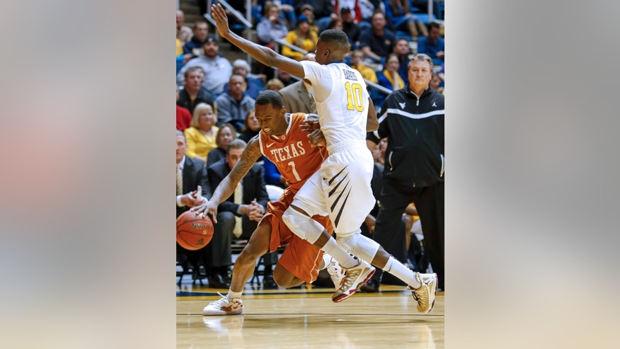 Texas' Sheldon McClellan (1) is fouled by West Virginia's Eron Harris (10) during the first half of an NCAA college basketball game at WVU Coliseum in Morgantown, W.Va., on Monday, Feb. 4, 2013. (AP Photo/David Smith)