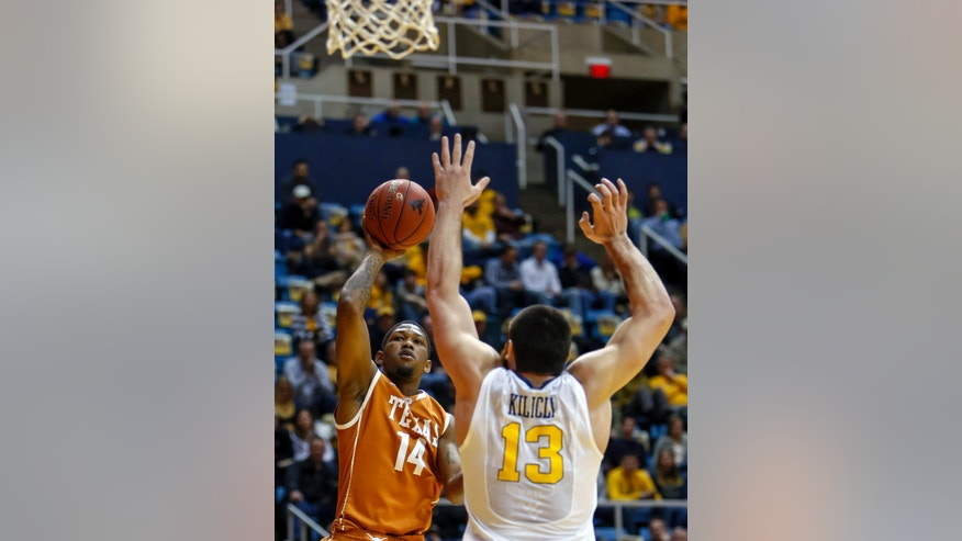 Texas' Julien Lewis (14) shoots over West Virginia's Deniz Kilicli (13) during the first half of an NCAA college basketball game at WVU Coliseum in Morgantown, W.Va., on Monday, Feb. 4, 2013. (AP Photo/David Smith)