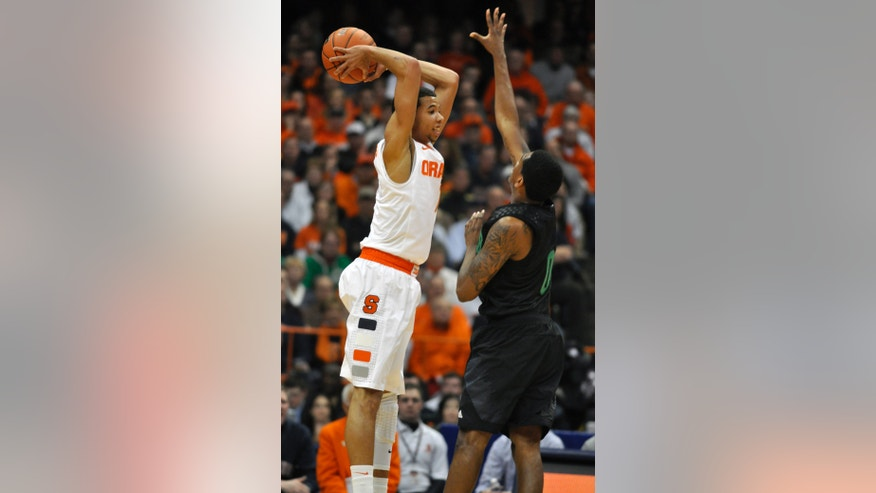 Syracuse's Michael Carter-Williams passes over Notre Dame's Eric Atkins during the first half of an NCAA college basketball game in Syracuse, N.Y., Monday, Feb. 4, 2013. (AP Photo/Kevin Rivoli)